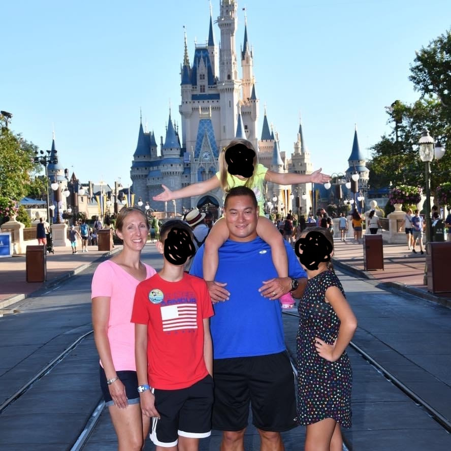 My dad, stepmom, and their three kids pose in front of Cinderella's castle.